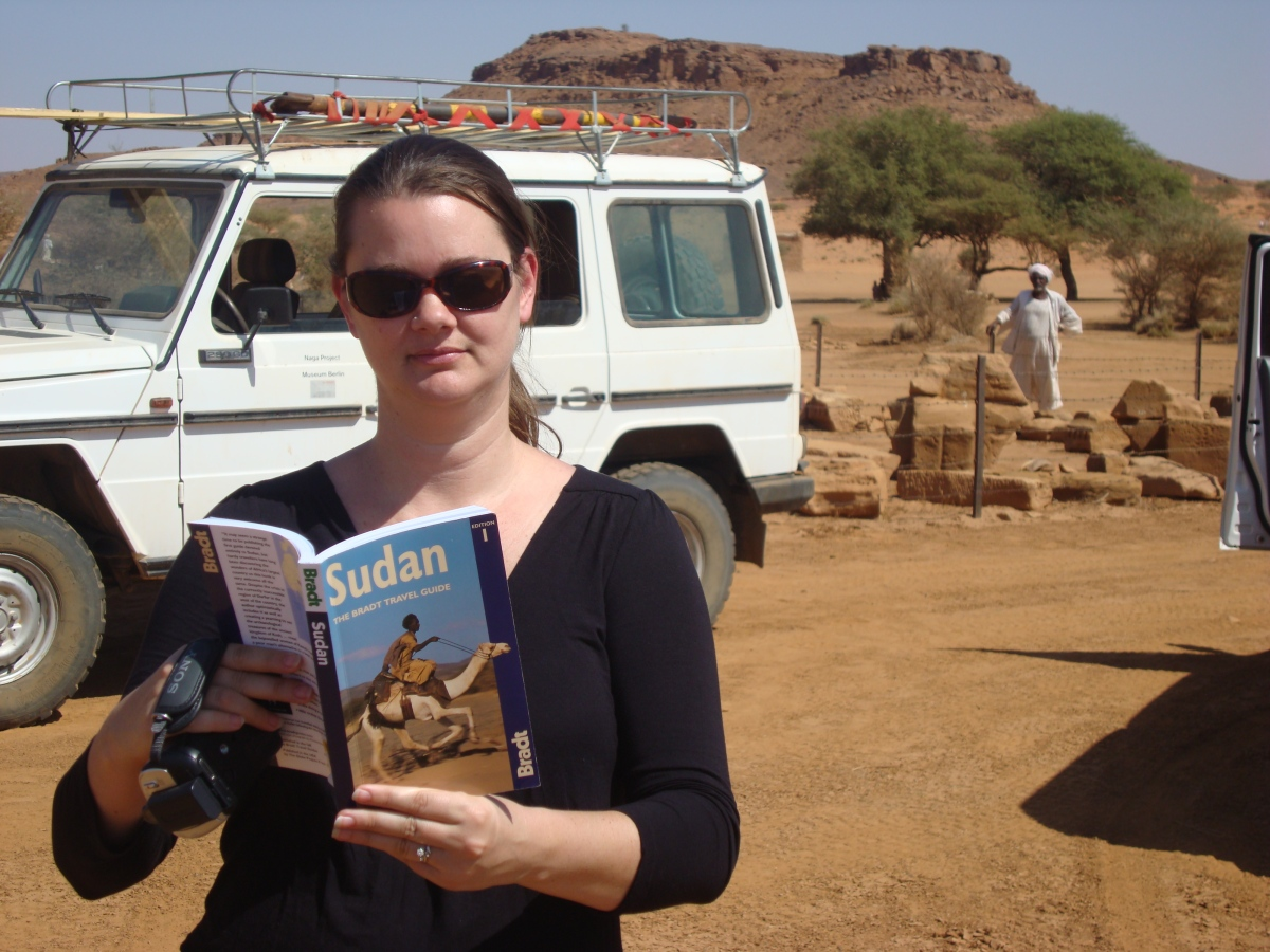 girl reading guidebook in desert in sudan