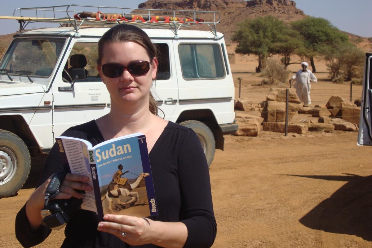 girl reading guidebook in desert in sudan
