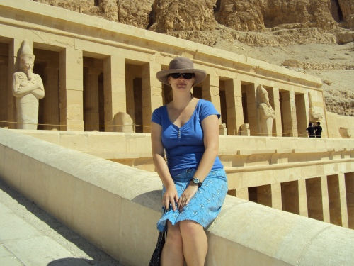 girl sitting in front of queen hetshepsut's temple in luxor egypt
