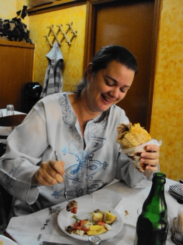 girl eating pork wrap in greece gyros