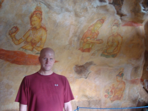 man in front of sigirya rock paintings sri lanka