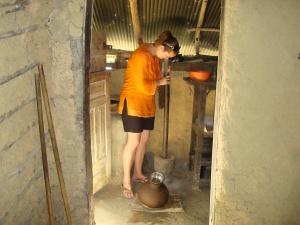 girl in orange shirt pounding cinnamon on sri lanka island