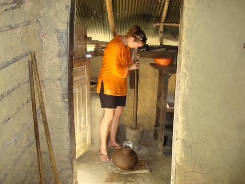 girl in orange shirt pounding cinnamon on sri lanka island
