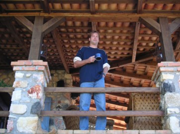 man standing with coffee cup stone house wood rafters