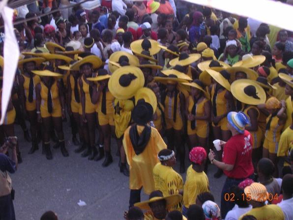 yellow and black hat ladies dancing at jacmel carnival haiti