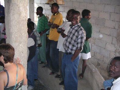 men standing around cockfight in Haiti