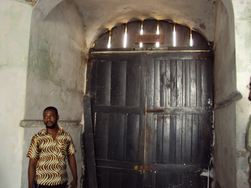 man standing in front of door of no return cape coast slave castle ghana