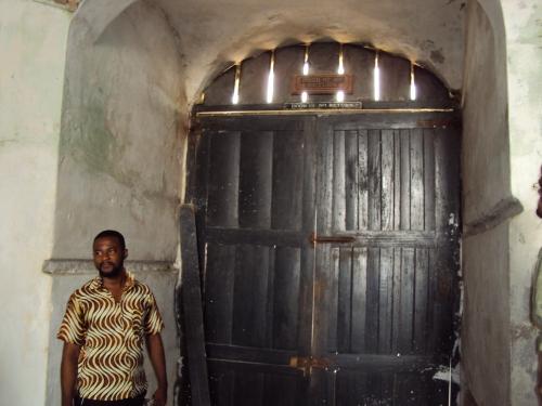 man standing in front of door of no return cape coast slave castle ghana