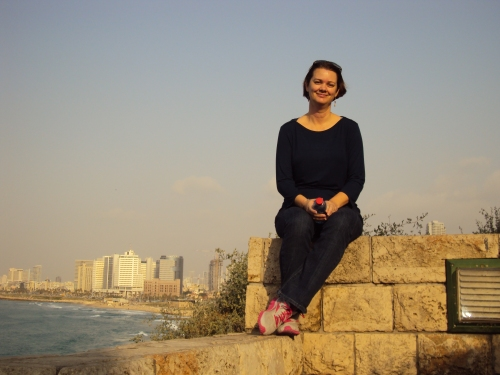 woman sitting on blocks with Tel Aviv Israel in background