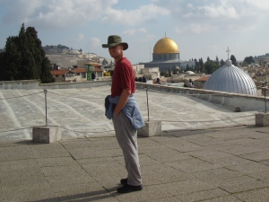 man standing on roof in israel overlooking gold dome
