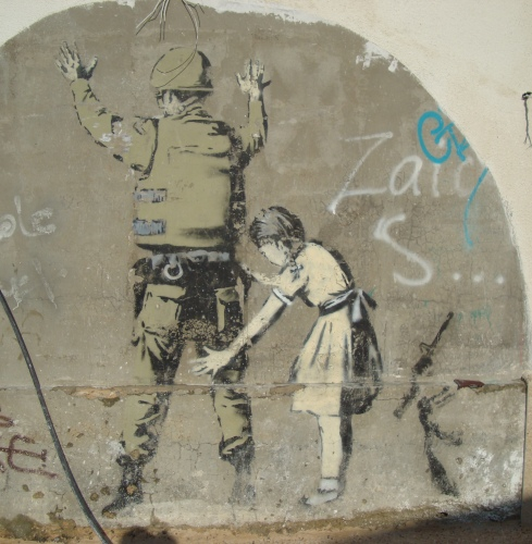 west bank street art palestine little girl patting down soldier banksy