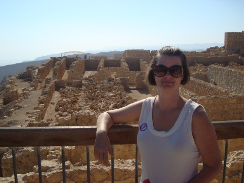 woman standing in front of Masada Israel fortress mountain top romans