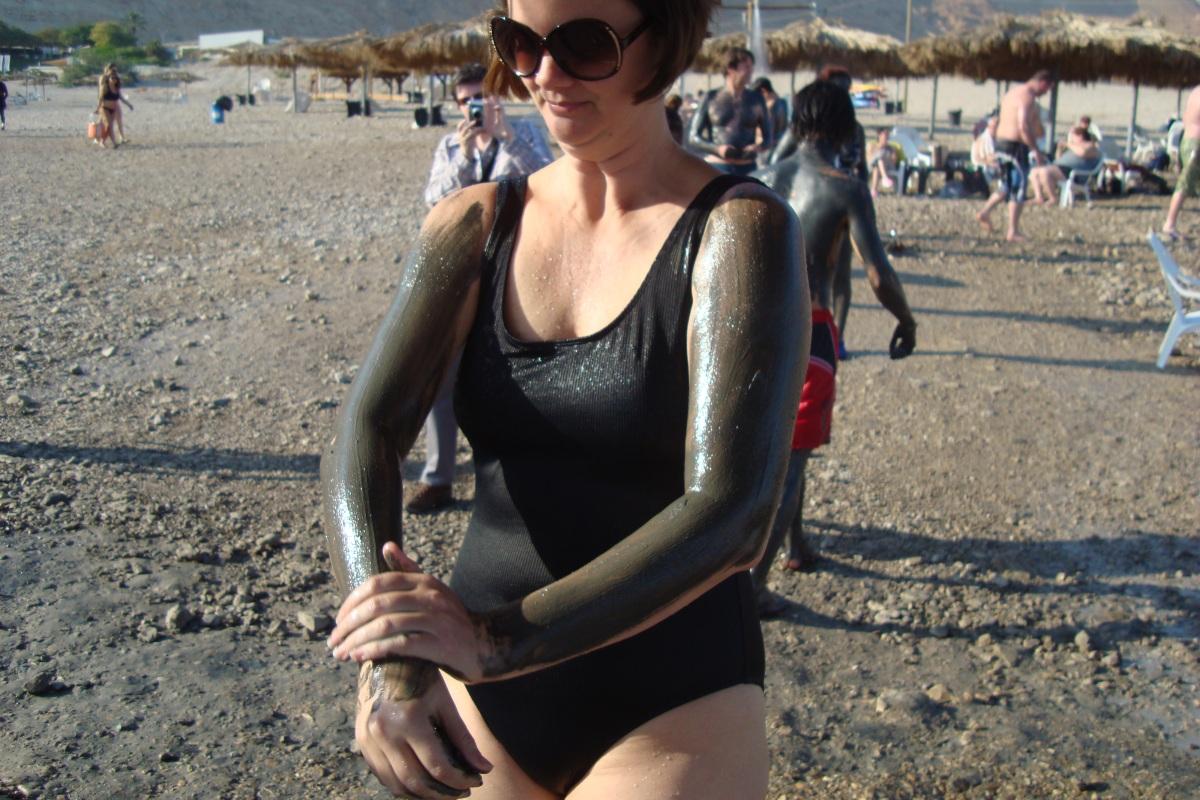 woman applying mud at dead sea israel