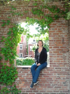 woman sitting on brick window wall with ivy