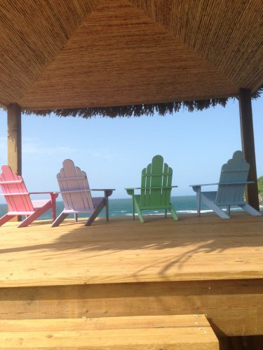 four colorful deck chairs overlooking ocean