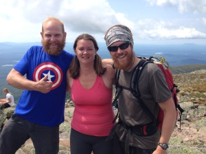 Three hikers finishing appalachian trail view from mount katahdin maine