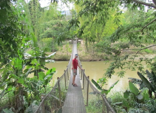 Chris on rope bridge over river in Papua New Guinea