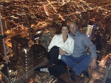 Couple sitting on glass floor Skydeck Chicago Willis Tower