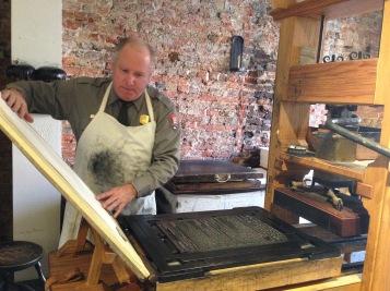 Park Ranger demonstrating a printing press at Ben Franklin's printing house