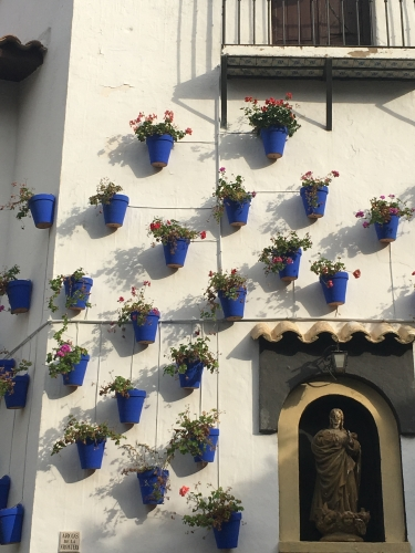 blue terra cotta pots outside white andalusian house