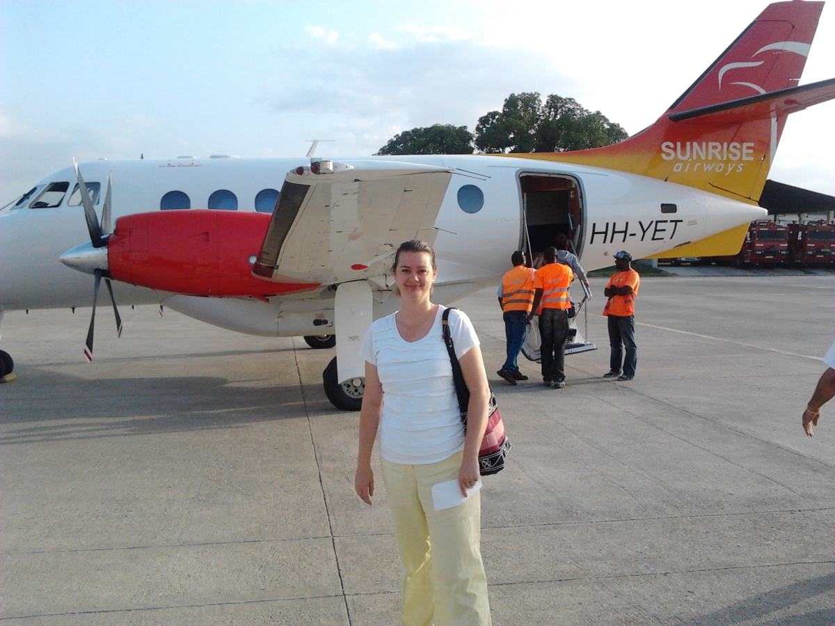 Deah in front of small plane in Haiti