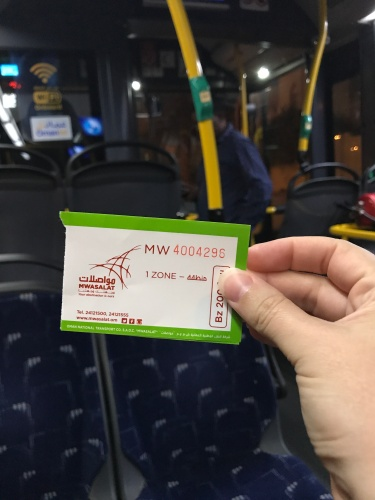 green and white mwasalat bus ticket on bus