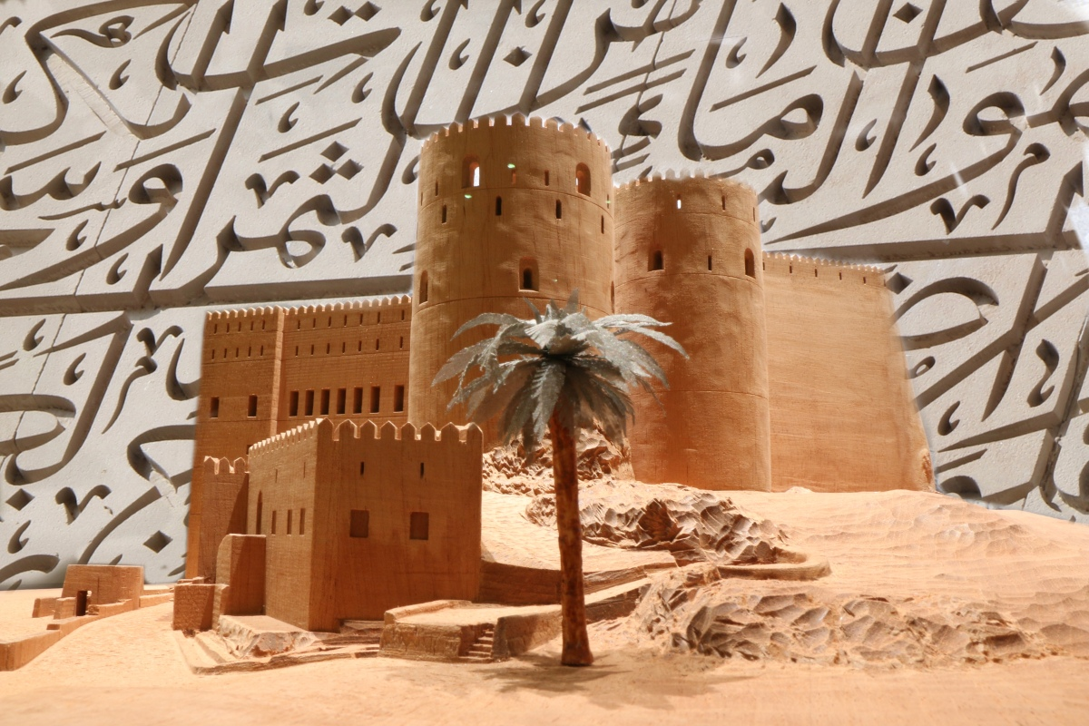 oman fortress model with arabic calligraphy in background