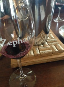 glass of red wine with cork trivet