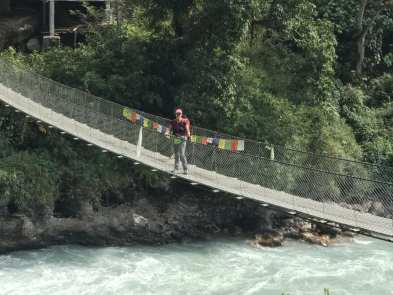 Deah at a bridge with prayer flags