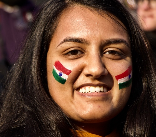 smiling woman with Indian face paint flag Wagah Border Ceremony