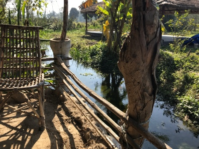 Wicker chair and railing along stream at farm in Rishikesh India