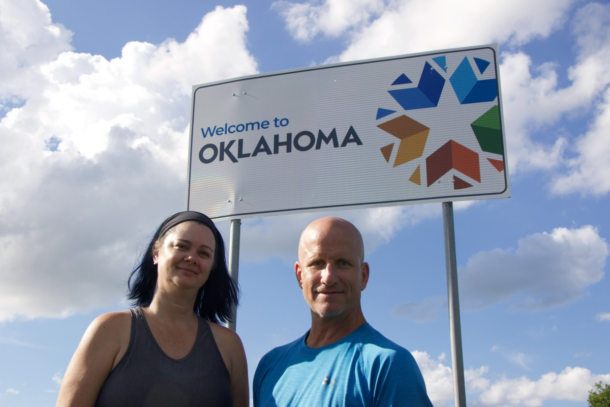 Deah and Chris standing in front of Welcome to Oklahoma Border sign